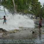 Wave floods over road during hige tide on Funafuti, Tuvalu.